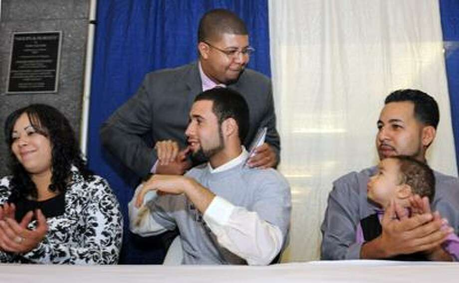 Hillhouse High School (New Haven) basketball player Freddie Wilson before signing a letter of intent to Seton Hall University surrounded by family and school staff. Left to right: his mother Gloryvee Rivera, Principal Kermit Carolina, Wilson, his stepdad Raymond Paret with his son Raymond age 1. Photo by Mara Lavitt/New Haven Register11/16/10