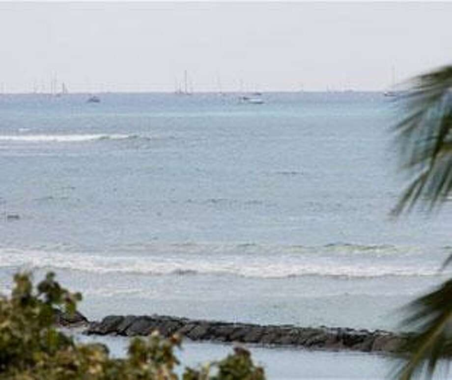 The tsunami wave brings the water back in covering the once exposed reef off Waikiki Beach in Honolulu Saturday, Feb. 27, 2010. A tsunami triggered by an earthquake in Chile swept ashore in Hawaii on Saturday, but the initial waves did not appear to cause significant damage. (AP Photo/Eugene Tanner)