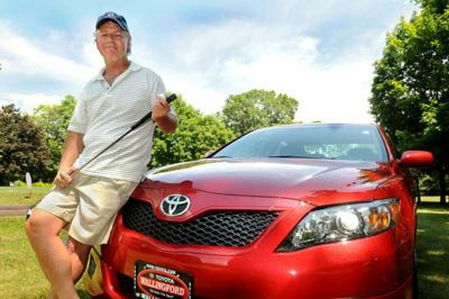 Patrick Riddle, of Shelton, shows off the Toyota that the won at the Walter Camp Golf Tournament in Wallingford. Riddle won the car by hitting a hole in one from the 16th tee.      Melanie Stengel/Register