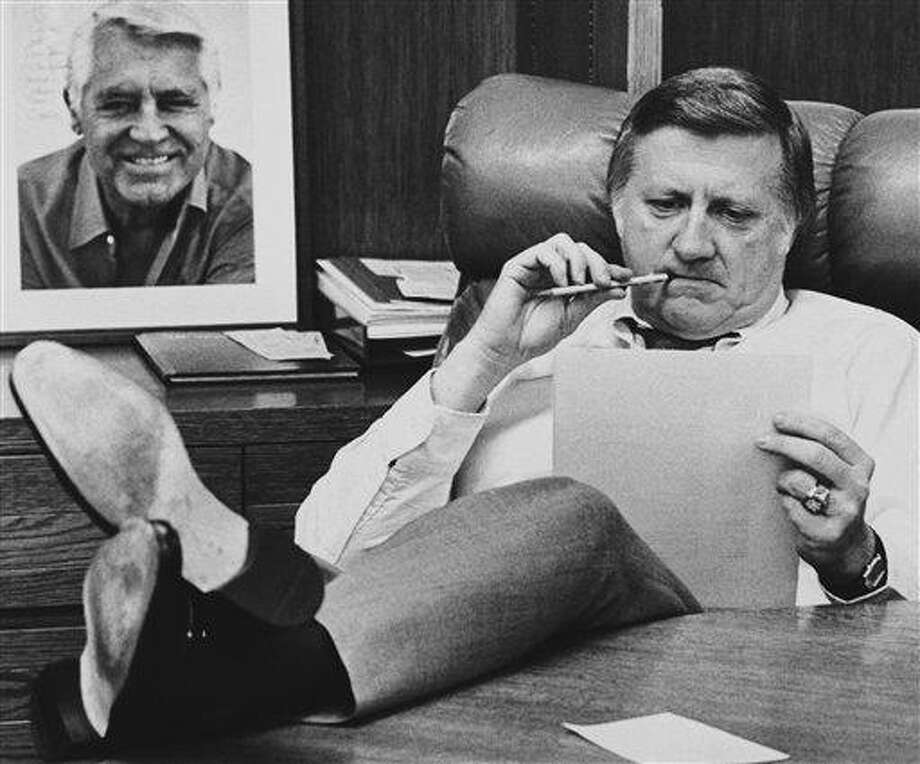 This Oct. 21, 1981, file photo shows New York Yankees owner George Steinbrenner working at his desk at Yankee Stadium in New York, before Game 2 of the World Series. On the wall behind Steinbrenner is an autographed photo of Cary Grant. A person close to George Steinbrenner says the Yankees owner died Tuesday morning, July 13, 2010. (AP Photo/File) Photo: AP / AP1981