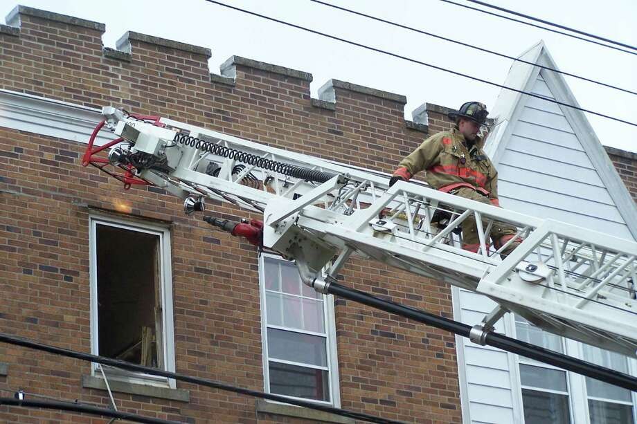 West Haven Fire Department firefighter John Perry climbs down the aerial ladder. Photo by Michael P. Walsh
