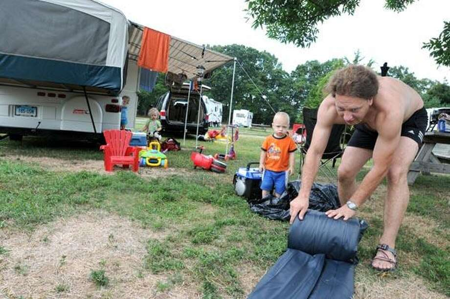 Patrick Mosur of New Britain, 2, watches his father Piotr Mosur roll up an air mattress as they pack up Friday during an evacuation of the campground at  Hammonasett State Park in Madison because of expected high winds from Hurricane Earl. (Peter Hvizdak/Register photos)