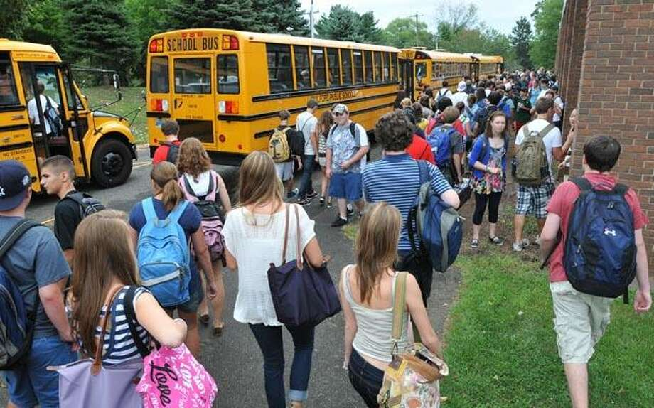 Students at Guilford High School head for the buses after an early dismissal spurred by the northward advance of Hurricane Earl. (Peter Casolino/Register)