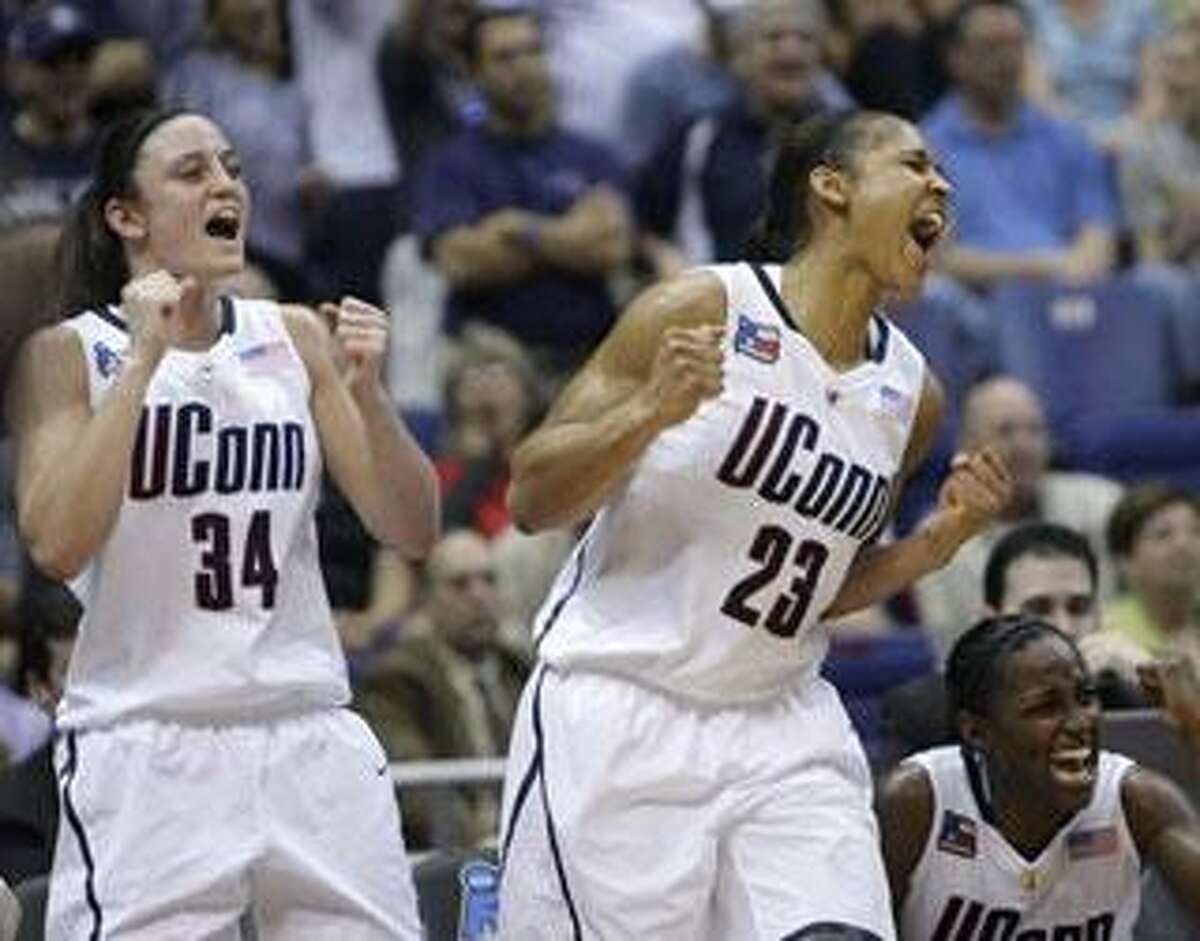 Connecticut's Kelly Faris (34), Maya Moore (23) and Kalana Greene, bottom right, celebrate in the closing seconds of Connecticut's 70-50 win over Baylor in a semifinal in the Final Four of the NCAA women's college basketball tournament Sunday, April 4, 2010, in San Antonio. Connecticut faces Stanford on Tuesday for the title. (AP Photo/Sue Ogrocki)