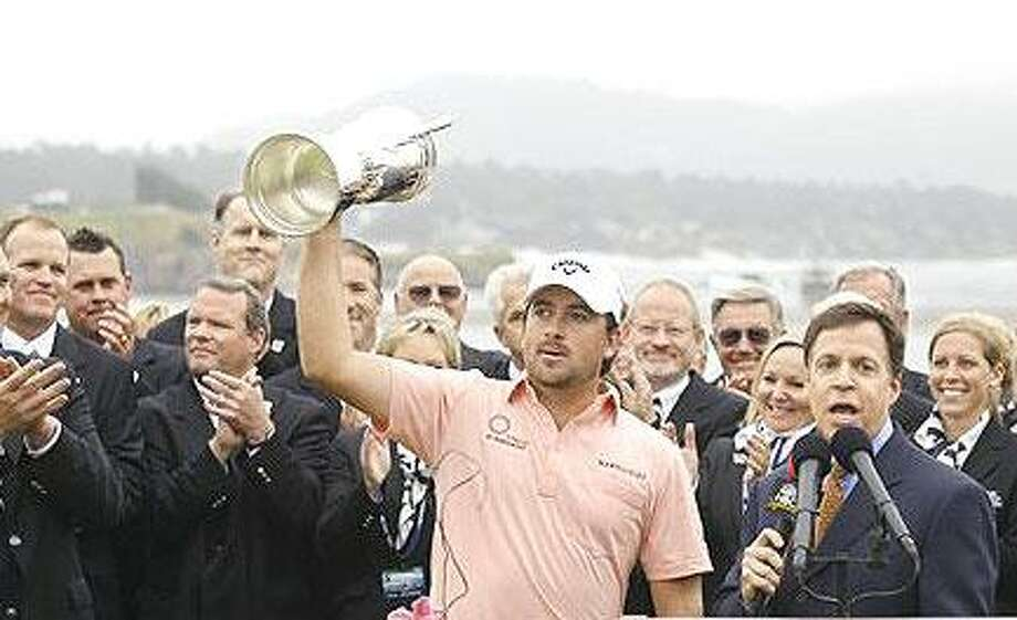 Graeme McDowell of Northern Ireland holds up the trophy after winning the U.S. Open golf tournament Sunday, June 20, 2010, at the Pebble Beach Golf Links in Pebble Beach, Calif. (AP Photo/Eric Risberg)
