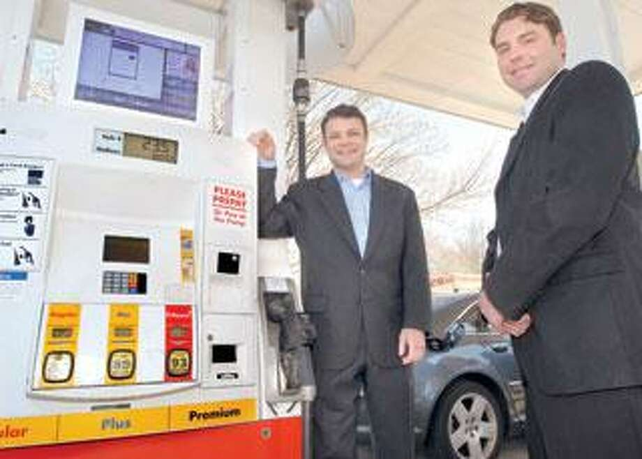 Entrepreneurs Ryan Duques, left, and James Warner, co-owners of IDTV, show off the technology at a Shell gas station in Guilford. The duo is selling advertising space on televisions being mounted atop gas pumps in the region. (Mara Lavitt/Register)