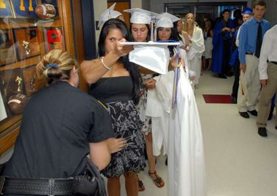 Seymour police Officer Christa Ventura pats down a graduating student while a line of girls behind her await their turn inside the school prior to commencement exercises Wednesday night. (Mara Lavitt/Register)