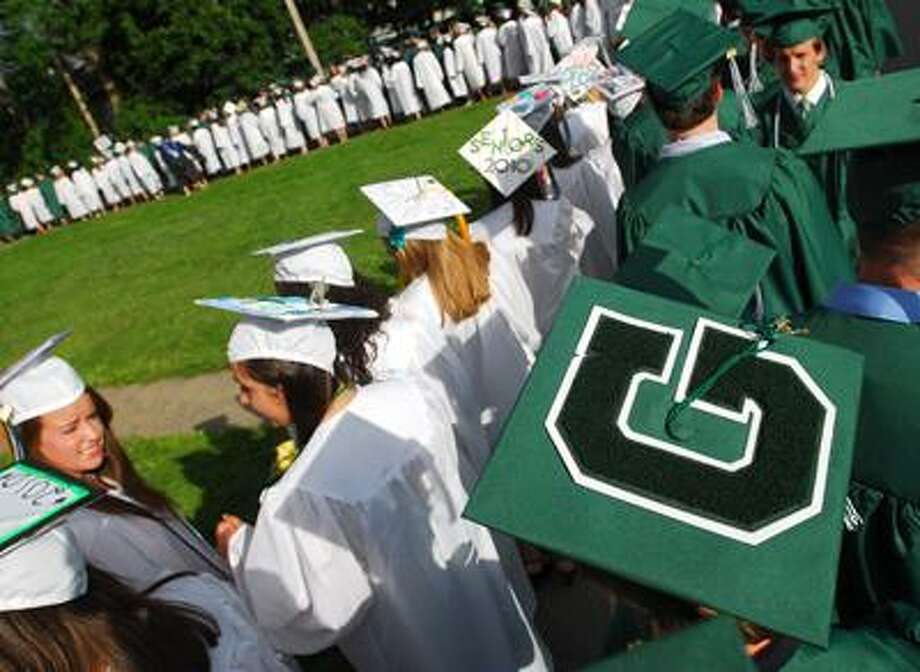 Guilford High School graduating seniors queue up behind St. George Catholic Church before moving to the Green for commencement. (Brad Horrigan/Register)