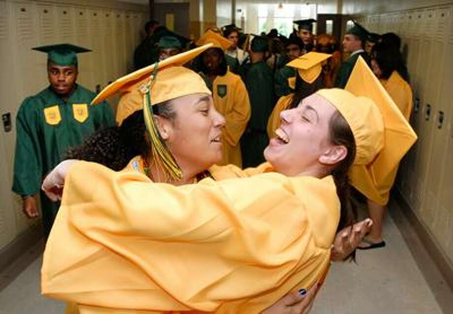 Hamden High graduates Symone Watson, left, and Katie Straka share a laugh as they prepare for their commencement ceremony at Hamden High School. (Peter Casolino/Register)