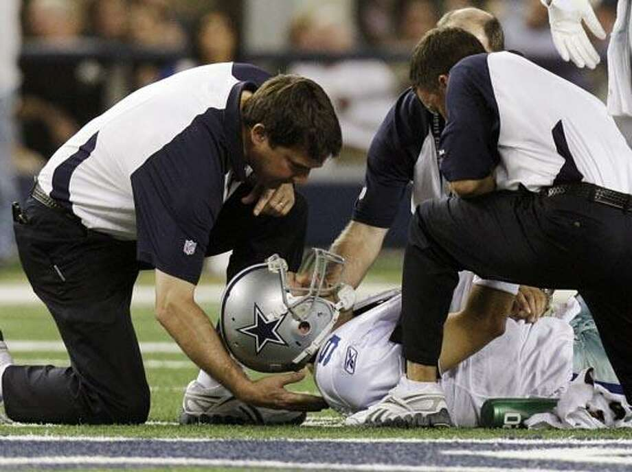 Dallas Cowboys quarterback Tony Romo is tended to during the first half of  against the New York Giants in an NFL football game Monday, Oct. 25, 2010, in Arlington, Texas. Romo was drilled into the turf on his left shoulder, forcing him to the locker room for X-rays. (AP Photo/LM Otero) Photo: AP / AP