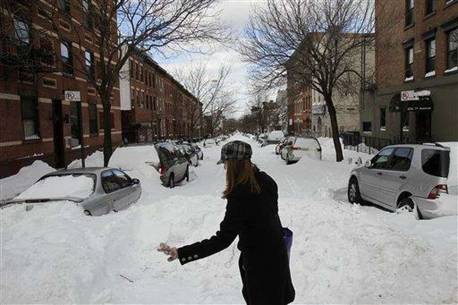 A woman makes her way gingerly through an intersection, past an unplowed street, in New York, Tuesday, Dec. 28, 2010. (AP Photo/Seth Wenig) Photo: AP / AP