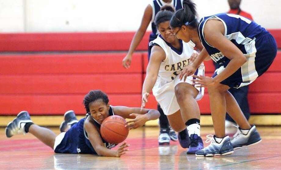 New Haven--Hillhouse's Ta'Kerra Williams dives for a lose ball during Tuesday's game against Career at Wilbur Cross High School.  At right is Hillhouse's Kalinka DeRoche and center, Career's Jasmine Claxton.  Photo by Brad Horrigan/New Haven Register-12.28.10.
