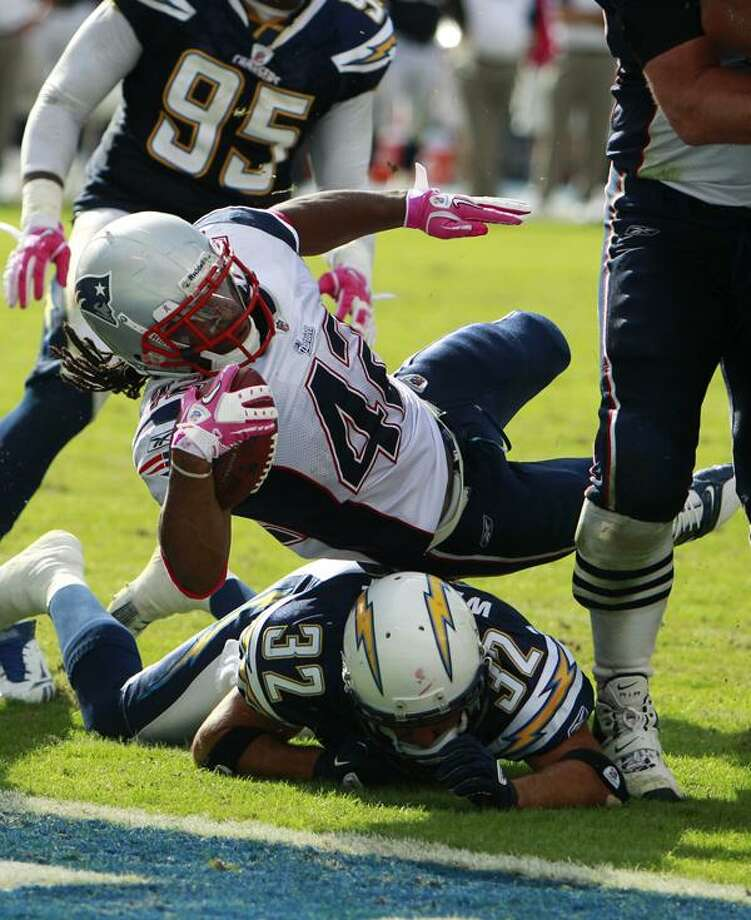 New England Patriots running back BenJarvus Green-Ellis is brought down before reaching the end zone, above San Diego Chargers safety Eric Weddle in the second half of an NFL football game Sunday, Oct. 24, 2010, in San Diego. (AP Photo/Lenny Ignelzi) Photo: AP / AP