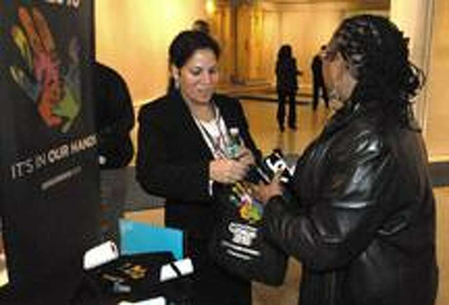 Census worker Maritza Gant, left, give Evette Hamilton a census goodie bag at Yale's Woolsey Hall Saturday for having completed and returned her 2010 U.S. Census form.  (Brad Horrigan/New Haven Register)