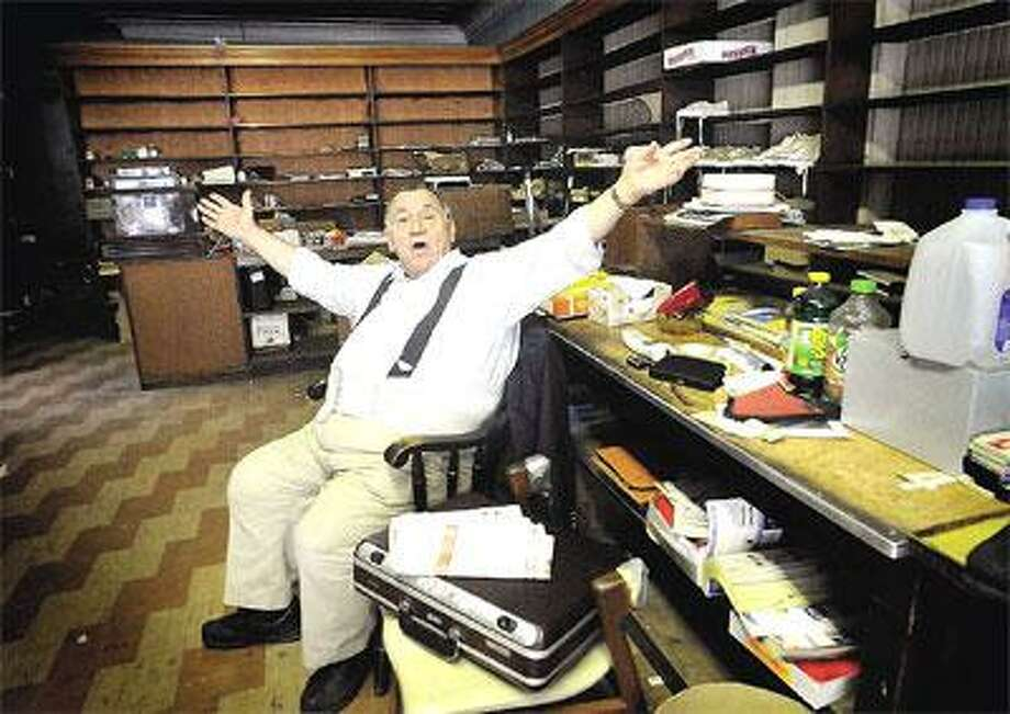 """Joe Maxner gestures and says """"these shelves were once full."""" He has been managing Rogol's since his friend and former owner of the Seymour men's clothing shop, Teddy Rogol, died more than two years ago. The store is closing in the next few weeks. (Melanie Stengel/Register)"""
