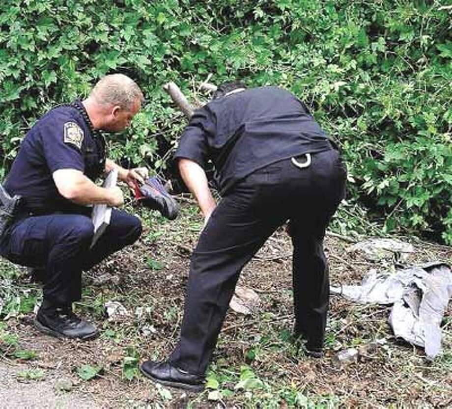 Hamden police Officer Richard Dziekan, left, and another officer look at a sneaker left at the scene of Wednesday evening's accident. (Peter Casolino/Register)