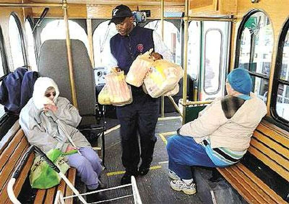Trolley driver Alston Walker helps riders board his bus in West Haven after a trip to Stop & Shop. Frances Przygocki, left, and Joan Ayotte are regular riders. (Mara Lavitt/Register)