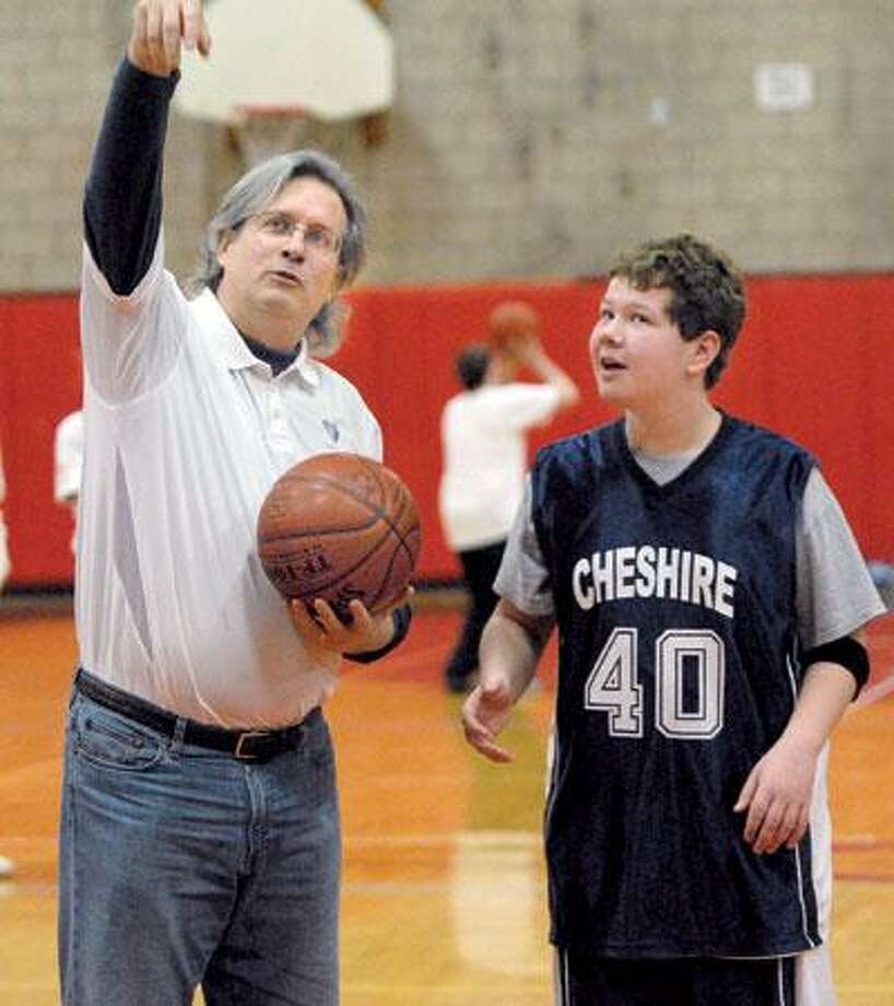 In 2009, Dr. Petit, left, gives some tips to Jack Hanrahan of Cheshire at the second annual Petit Family Memorial Basketball Tournament at Cheshire High School. (Mara Lavitt/Register file)