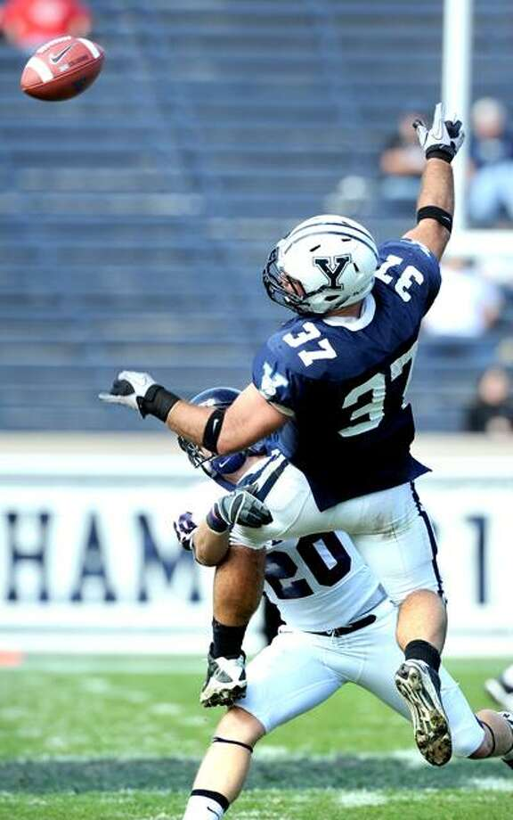 Shane Bannon can't reach a pass while being defended by Penn's Jason Schmucker during the second half of the Quakers' 27-20 win Saturday at the Yale Bowl. (Arnold Gold/Register)