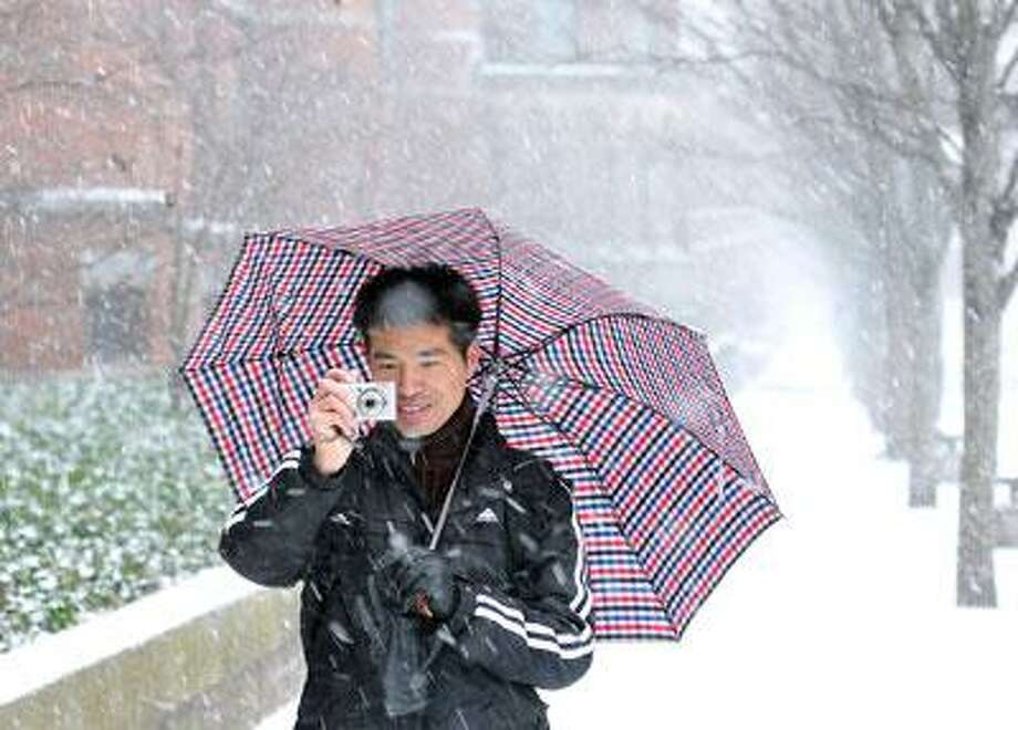 """Yale Medical student XinXiang Lei takes photos of the snow along College Street in New Haven as the blizzard started early Sunday afternoon. Lei, who is from southern China and doesn't see much snow in his native country. """"It's beautiful!"""" said Lei.  (Photo by Peter Casolino/New Haven Register)"""