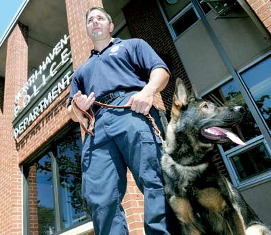 North Haven Police Officer James Brennan is photographed with his new 18-month-old German shepherd police dog, Zeus, in front of the North Haven Police Department recently. (Arnold Gold/Register)