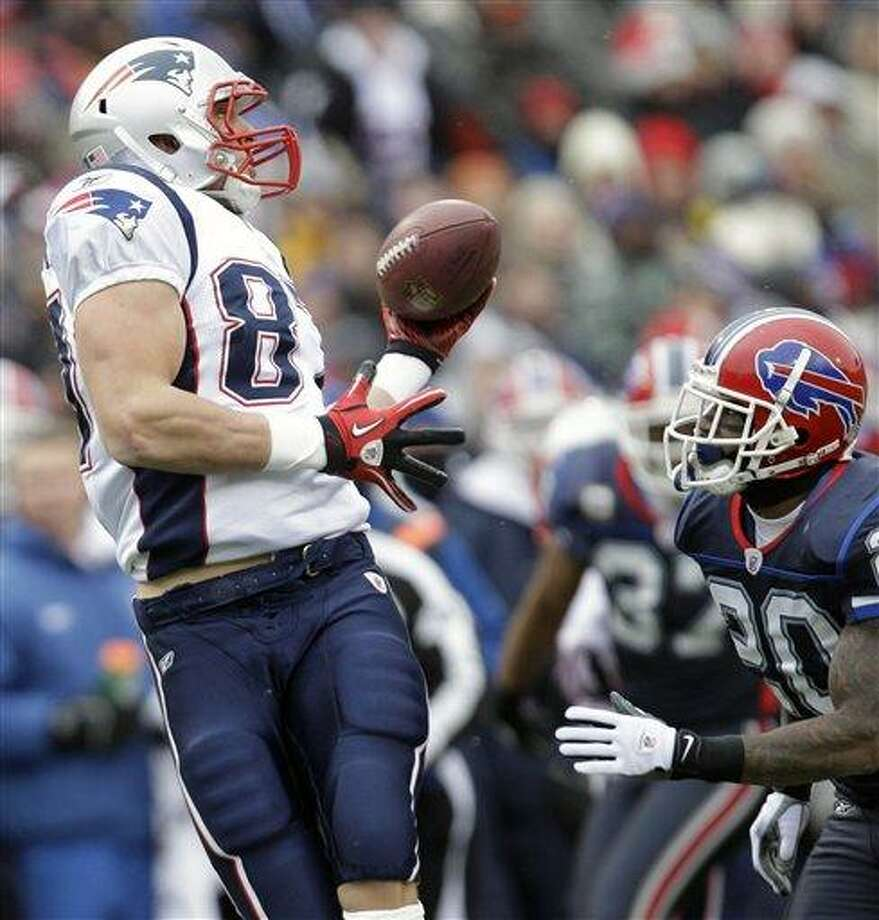 New England Patriots' Rob Gronkowski (87) makes a catch under pressure from Buffalo Bills' Donte Whitner (20) during the first half of an NFL football game in Orchard Park, N.Y., Sunday, Dec. 26, 2010. (AP Photo/David Duprey) Photo: AP / AP