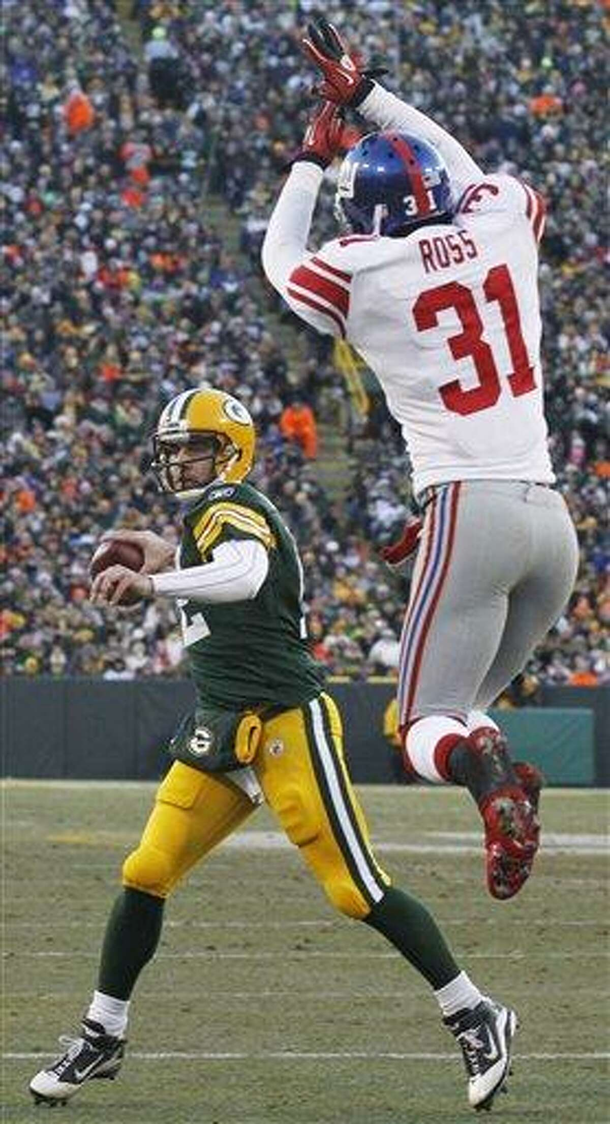New York Giants' Aaron Ross (31) applies pressure as Green Bay Packers quarterback Aaron Rodgers (12) throws a 3-yard touchdown pass to James Jones during the first half of an NFL football game Sunday, Dec. 26, 2010, in Green Bay, Wis. (AP Photo/Jeffrey Phelps)