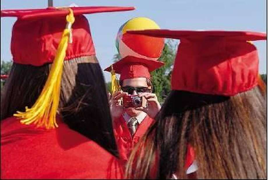 Brad Horrigan/Register  Lucas Cecchetto, center, photographs two classmates at Branford High School before going to commencement exercises on the Branford Green.
