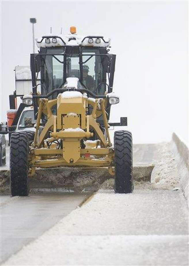 A road grader pushes snow and ice to the side of the Hudson Memorial river bridge in Decatur, Ala. on Christmas morning, Saturday, Dec. 25, 2010. Residents of Decatur awoke to a rare Christmas morning snow. (AP Photo/The Decatur Daily, Brennen G. Smith) Photo: AP / The Decatur Daily