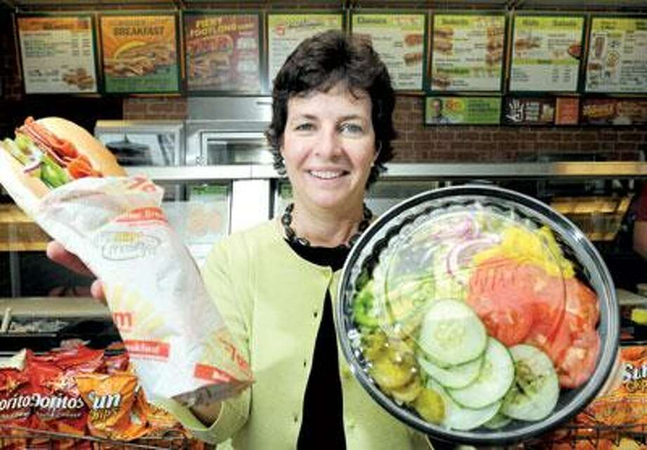 Elizabeth Stewart, Subway's marketing director for corporate responsibility, holds a 12-inch sub and salad at a Subway restaurant in Milford. The paper the sub is wrapped in as well as the salad bowl are made in part from recycled materials. The chain has a growing focus on 'green' measures. (Arnold Gold/Register)
