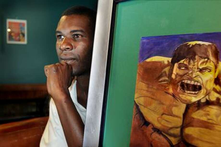 Tizzie Mills with one of his paintings on display at the Blue State Coffee Shop in New Haven. He sold some paintings at a show there, but was mugged on his way home.  Melanie Stengel/Register