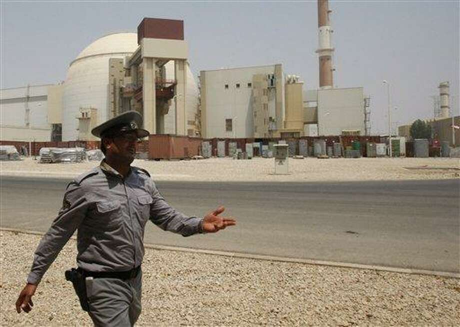 An Iranian security directs media at the Bushehr nuclear power plant, with the reactor building seen in the background, just outside the southern city of Bushehr, Iran, Saturday, Aug. 21, 2010. Iranian and Russian engineers began loading fuel Saturday into Iran's first nuclear power plant, which Moscow has promised to safeguard to prevent material at the site from being used in any potential weapons production. (AP Photo/Vahid Salemi) Photo: AP / AP
