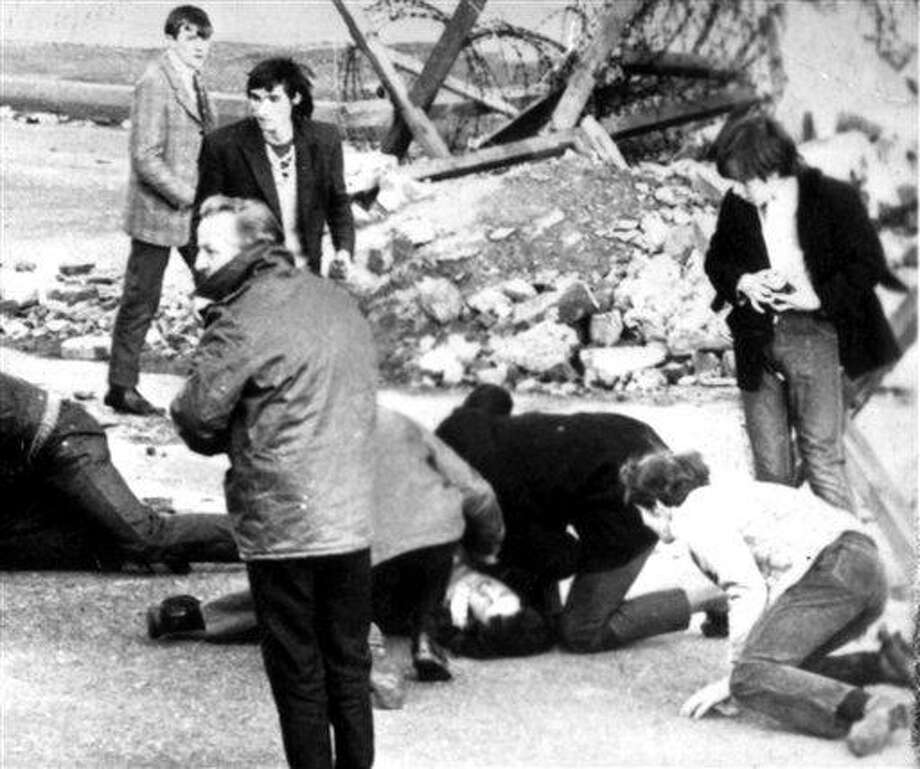 In this Sunday, Jan. 31, 1972, file photo, a man receives attention during the shooting incident in Londonderry, Northern Ireland, which became known as Bloody Sunday. An epic 12-year investigation into Northern Ireland's biggest mass killing by British soldiers reached a bittersweet climax Tuesday as relatives of the 13 Catholic demonstrators killed began reading a 5,000-page report into why the 1972 slaughter happened. (Associated Press) Photo: ASSOCIATED PRESS / PAMPC PA