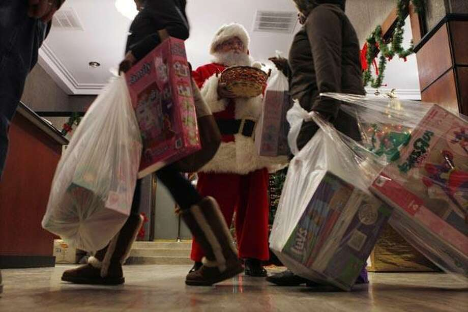 In this photo taken Friday, Dec. 17, 2010, people with packages walk past Santa John Wenner as he greets people in Friday, Dec. 17, 2010, in Philadelphia. Freelance Santas report that they have fewer _ if any _ bookings this season, largely because of the economy. (AP Photo/Mel Evans) Photo: AP / AP