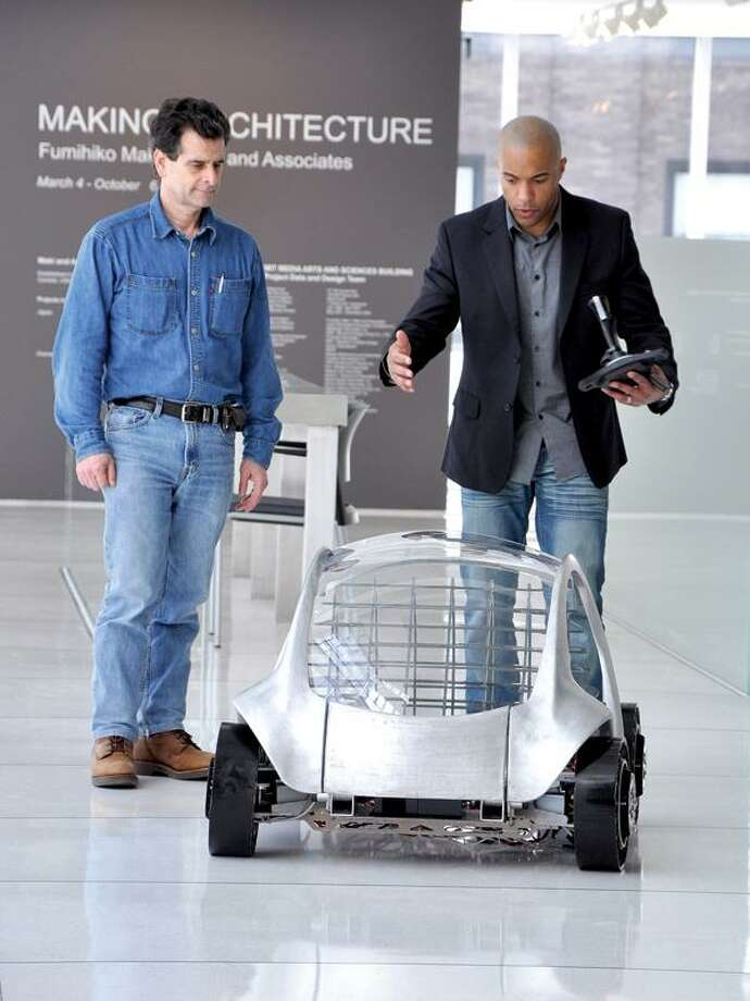 """Planet Green photo, William Lark, right, shows off the CityCar prototype to inventor Dean Kamen at MIT Media Lab's Smart Cities Research Group in Cambridge, Mass., during the taping of the series """"Dean of Invention,"""" which debuts Friday."""
