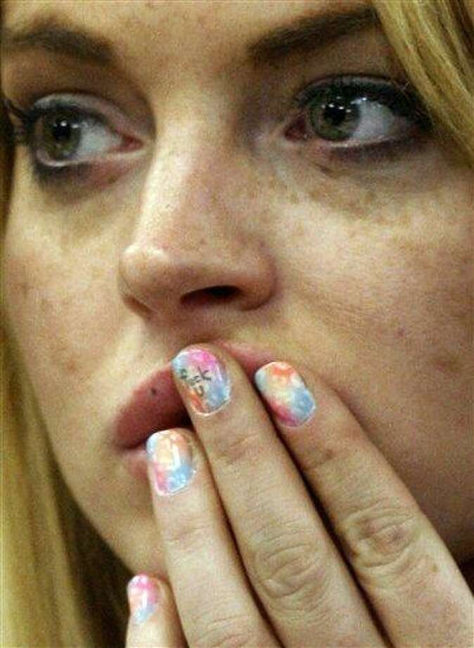 ** EDS NOTE: OBSCENE LANGUAGE ON LEFT MIDDLE FINGERNAIL -- FOR USE AS DESIRED, YEAR END PHOTOS ** FILE -In this July 6, 2010 file photo, profane language is seen on the middle fingernail of actress Lindsay Lohan during a hearing in Beverly Hills, Calif. The judge sentenced Lindsay Lohan to 90 days in jail Tuesday after ruling she violated probation in a 2007 drug case by failing to attend court-ordered alcohol education classes. (AP Photo/David McNew, Pool, File) Photo: AP / AP2010