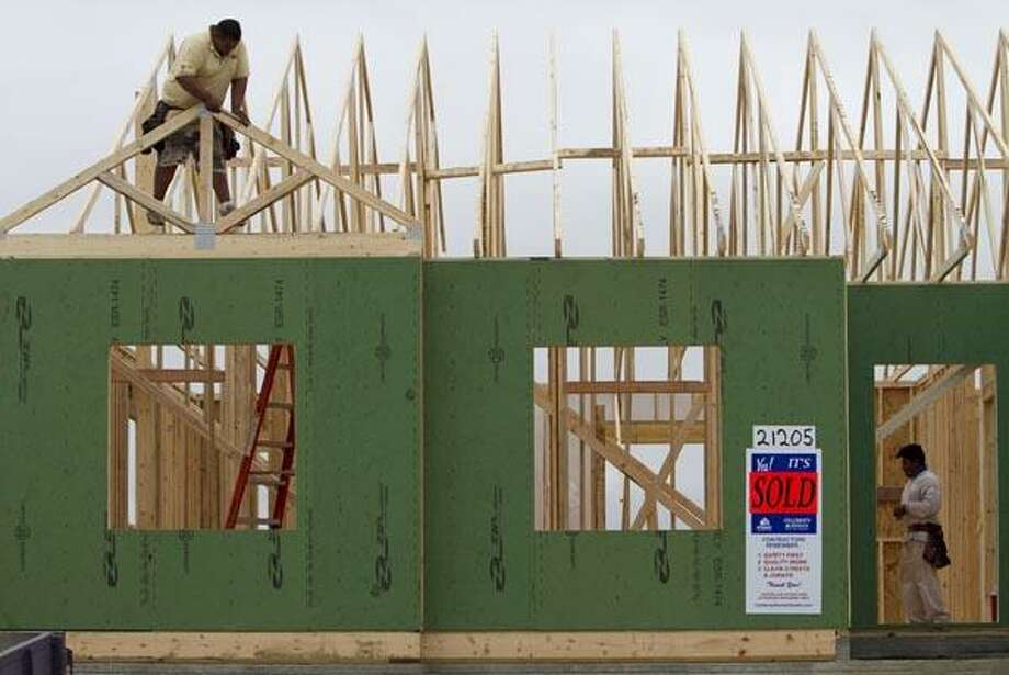 In this Sept. 16, 2010 photograph, builders work on a home in Gretna, Neb., where a sign declares the home sold. Home construction rose slightly last month on the strength of single-family homes, but the market was still too weak to propel growth in the battered industry.(AP Photo/Nati Harnik) Photo: AP
