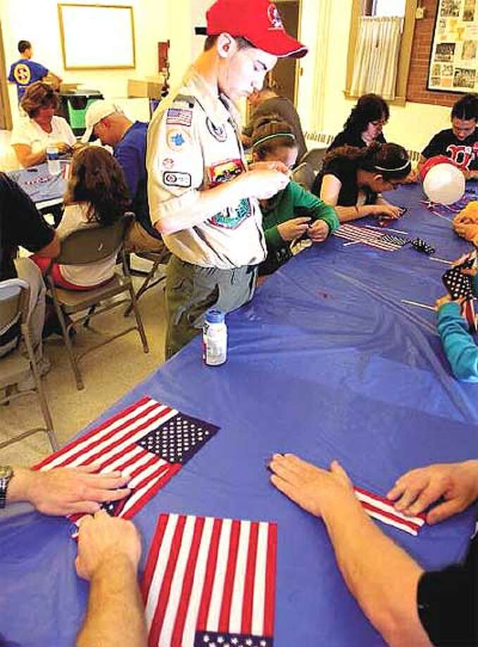 """Michael Brainerd, 15, a member of the Columbian Squires and a Boy Scout, along with the church's """"Leap of Faith"""" youth group, fold the flags that will be packed with a prayer card and sent to troops. (Peter Hvizdak/Register)"""