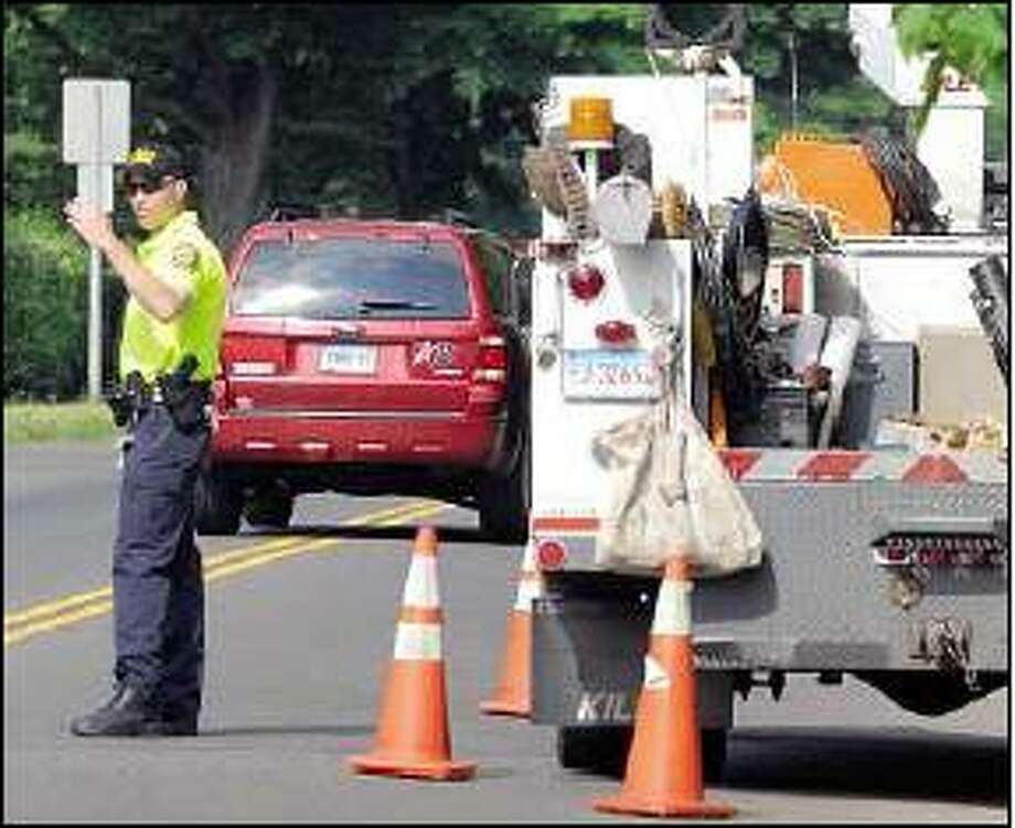 Peter Hvizdak/Register  Hamden Police Chief Thomas J. Wydra directs traffic at a work site at the corner of Whitney and Putnam avenues on June 5.