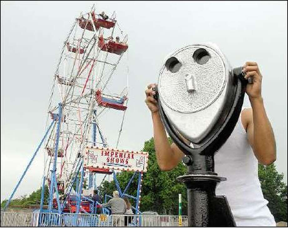 Klever Encalada looks out over New Haven using coin-operated binoculars from the summit of East Rock Saturday afternoon. The Ferris wheel was part of the East Rock Festival.  Brad Horrigan/Register