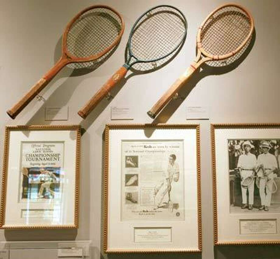 Tennis rackets from the  1920s are seen above historic photos  at the museum.