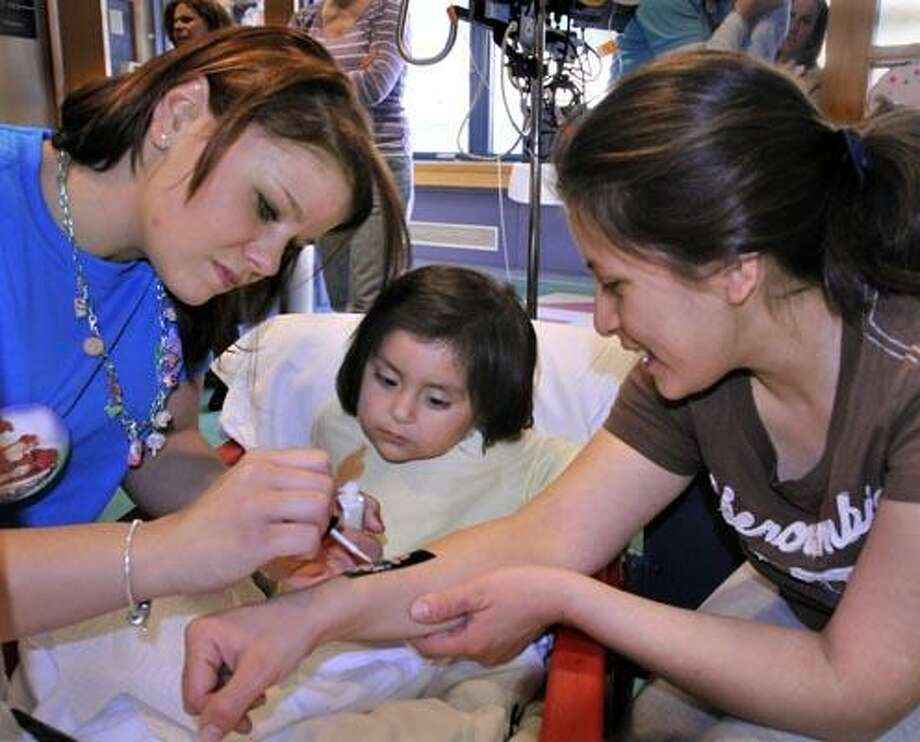 """New Haven-- Marguerite Swan (L), of Sundae Spa, paints a holiday  """"tattoo"""" on Mayra Gallegos, of Danbury (R) as her daughter Melody Galarza, 1 1/2, looks on.  Sundae Spa came to Yale-New Haven Children's Hospital  as a holiday treat for children and their families.    Melanie Stengel/Register12/20/10"""