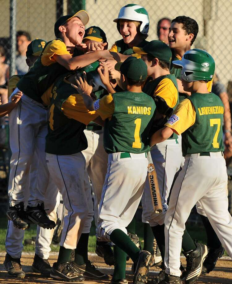 Michael Ficano's Shelton American teammates congratulate him at the plate after his solo home run in a win over Orange on July 26. (Brad Horrigan/Register file photo)