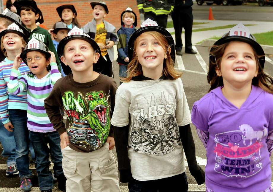 Front, l to r: Clara Rahner, Amelia Flores, Dillion Ridgeway, Erica Collenese, and Amilia Santanelli watch as New Haven firefighters in a hook and ladder truck bucket, rise above their school. They are all 1st graders at Nathen Hale Elementary School.     Melanie Stengel/Register