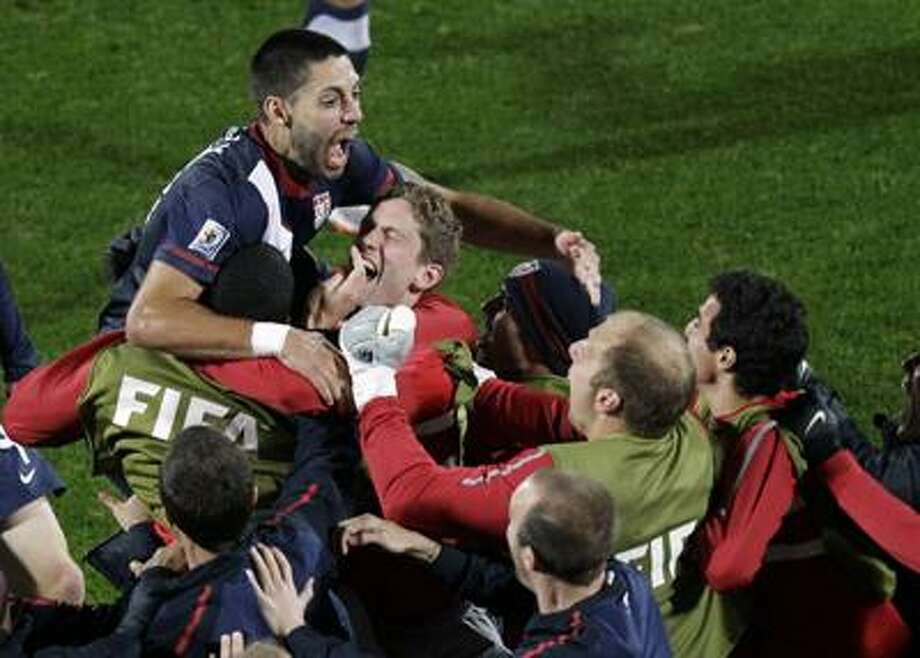 Clint Dempsey, top left, celebrates with his USA teammates after scoring the tying goal during the World Cup Group C soccer match against England Saturday at Royal Bafokeng Stadium in Rustenburg, South Africa. (AP Photo/Michael Sohn) Photo: AP / AP