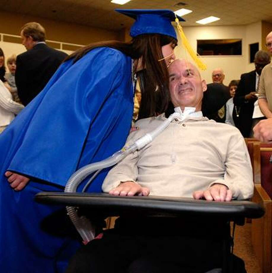 Kathleen McClain gives her father, David, a kiss as she processes into the West Woods Christian Academy commencement ceremonies (Held at the Gateway Christian Fellowship). David has Lou Gerhig's disease and surprised Kathleen by attending the graduation.  (Peter Casolino/Register)