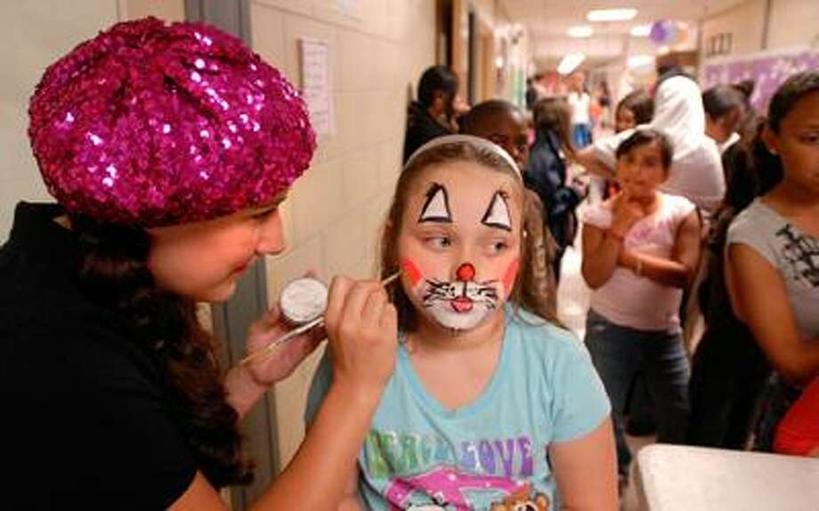 """Nine-year-old Carly Saunders, a second-grader at Molloy School in West Haven, gets her face painted by Jennifer Peterson of """"Painted You"""" in West Haven during the school's end-of-the-year picnic Thursday. This is the school's last picnic as it will be closed after school ends this year. Carly will attend Mackrille School next year for third grade. Said Carly, """"I'm going to miss all my friends."""" (Peter Casolino/Register)"""