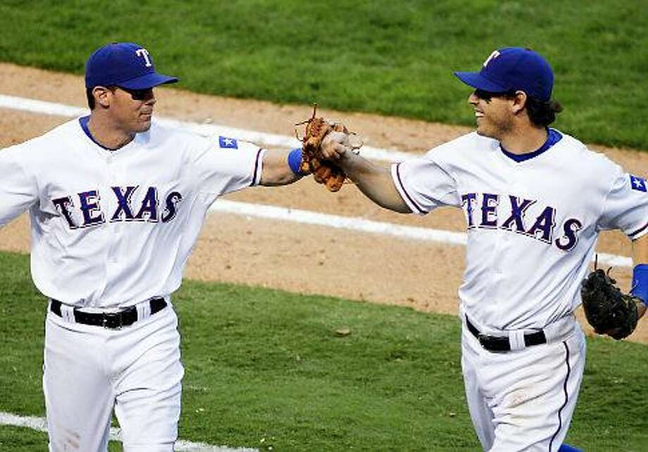 Third baseman Michael Young (l.), second baseman Ian Kinsler and the Rangers rebound immediately, and win Game 2 convincingly, despite a devastating loss to the Yankees on Friday. Sancya/AP