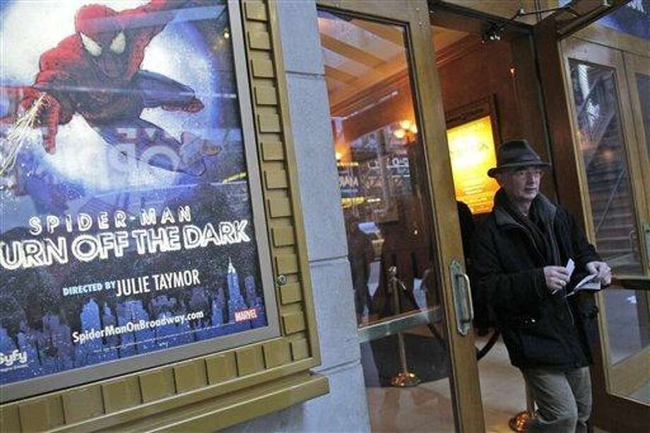 """Tom Zahner, of Cologne, Germany, leaves the Spider Man box office after purchasing tickets, Tuesday, Dec. 21, 2010 in New York.  The troubled Broadway musical """"Spider-Man: Turn Off the Dark"""" was plagued by its fourth accident since it began previews last month when a performer doing an aerial stunt fell about 30 feet, fire officials said.(AP Photo/Mary Altaffer) Photo: AP / AP"""