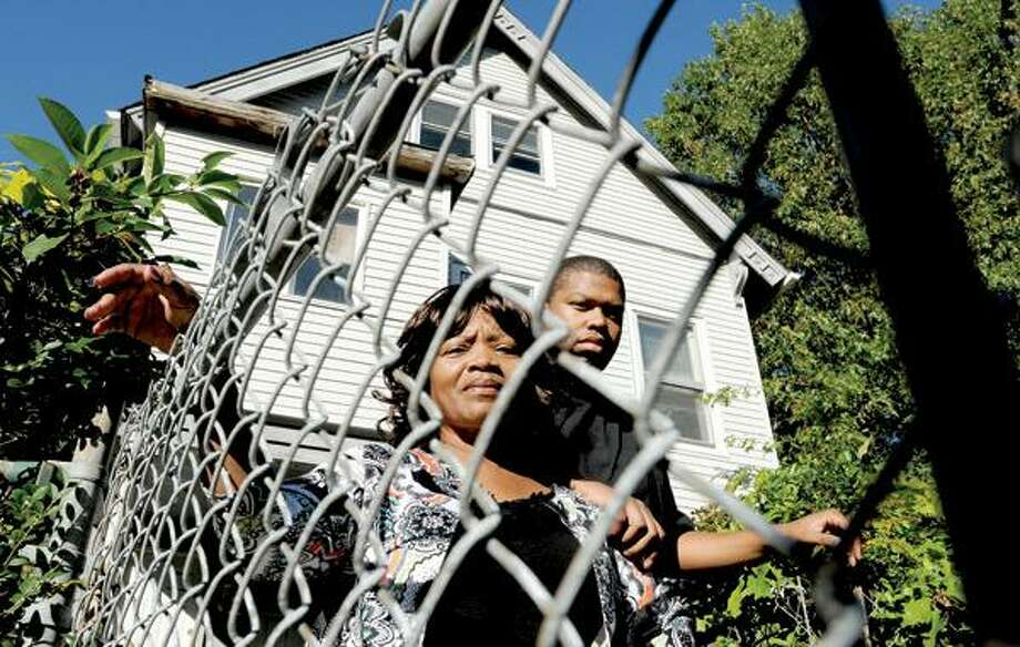 Peter Hvizdak/Register photo, Willie Darden Jr. and his mother, Mary Henderson, at the Thompson Street house he inherited from his father. He's been trying to stave off foreclosure for a year.